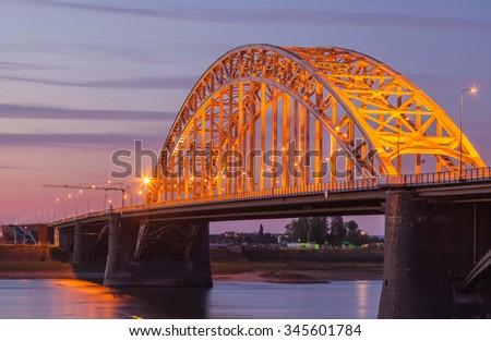 Beautiful bridge at twilight across Waal river - stock photo
