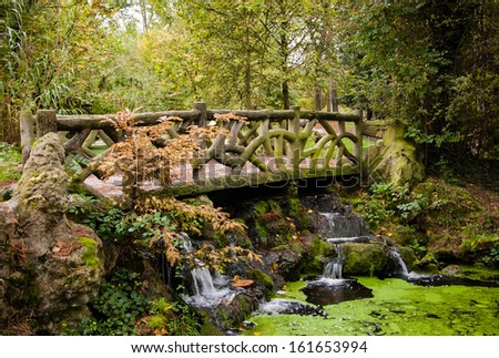 Beautiful bridge over the forest stream fitting perfectly into the environment. Autumn in Vincennes forest. (Paris, France). - stock photo
