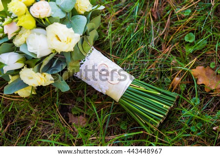 beautiful bright bouquet and rings on the grass