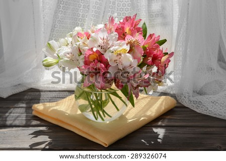 Beautiful bright bouquet in vase on fabric background - stock photo