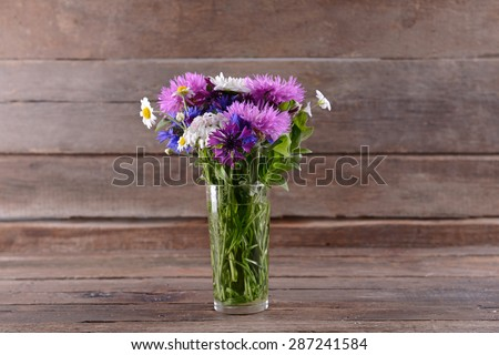 Beautiful bright bouquet in vase on wooden background - stock photo