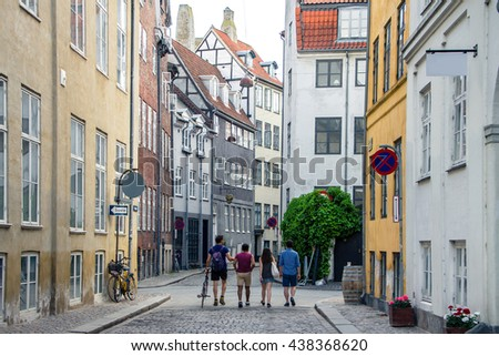 Beautiful bright cityscape in perspective. View on cobbled street with bicycles. Narrow street with colorful buildings in old historic center of Copenhagen. Red tiled roofs. Four people men go forward - stock photo
