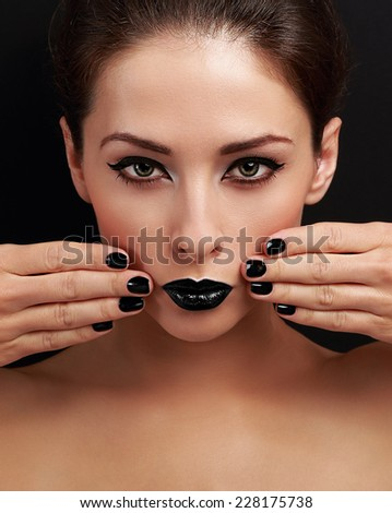 Beautiful bright evening makeup woman, black nails polish and black lipstick looking serious on black background - stock photo