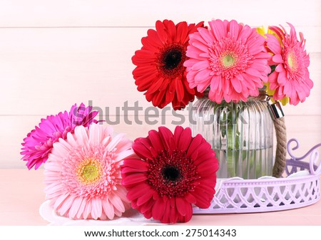 Beautiful bright gerberas in vase on wooden background