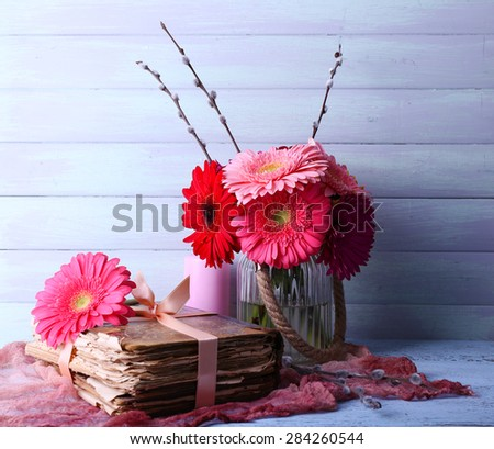 Beautiful bright gerberas in vase with old books on wooden background - stock photo