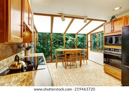 Beautiful bright kitchen interior. Dining area with transparent glass wall and vaulted ceiling
