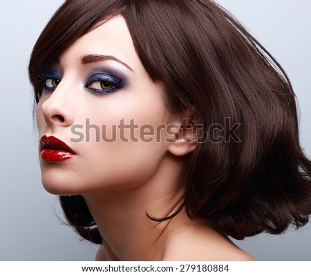Beautiful bright makeup with blue eyeshadow and red lipstick. Short hair style. Closeup - stock photo
