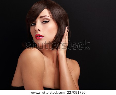 Beautiful bright makeup woman holding hand the short healthy hair and looking sexy on black background with empty copy space - stock photo