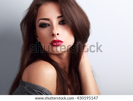 Beautiful bright makeup woman with red lipstick looking hot on blue background. Closeup portrait