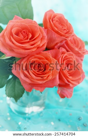 Beautiful bright orange roses in clear glass - stock photo