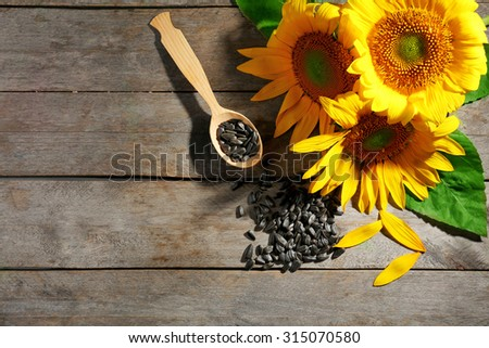 Beautiful bright sunflowers with seeds on wooden table close up - stock photo