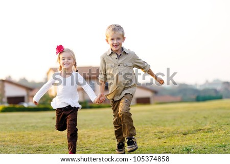 Beautiful brother and sister running and laughing together outdoors in a field with a suburban home in the background - stock photo