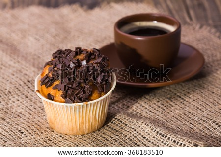 Beautiful brown cup of coffee on plate and fresh delicious cupcake bakery decorated by chocolate crumb in paper form appetizing treat for break on brown canvas background indoor closeup, horizontal - stock photo
