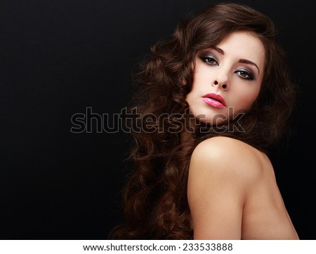 Beautiful brown curly hair woman looking. Closeup on black background with empty copy space - stock photo