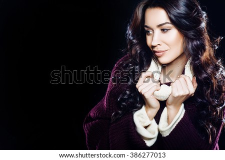 beautiful brown-eyed brunette girl model smiling with natural makeup and hair in a warm sweater on a black background