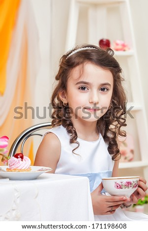 Beautiful brown-eyed girl drinking tea with sweets