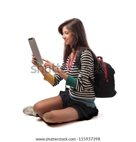 Beautiful brown girl, with a backpack, using a tablet pc