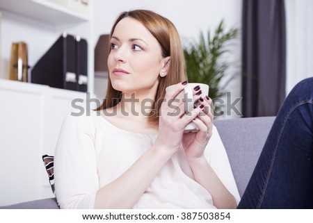 Beautiful brown haired girl having a rest on couch enjoying her mug with coffee or tea - stock photo