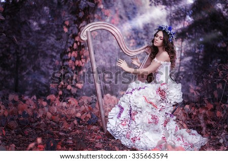 beautiful brown-haired woman with a flower wreath on her head, wearing a white dress playing the harp in the forest  - stock photo