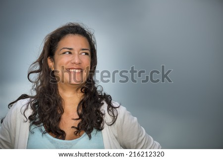 Beautiful brown young woman (20s) looking to the right with smiling. Head and shoulders on cloudscape background. Right copy space. - stock photo