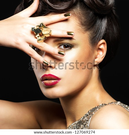 Beautiful brunet woman with golden nails and style makeup of eyes -  on black background - stock photo
