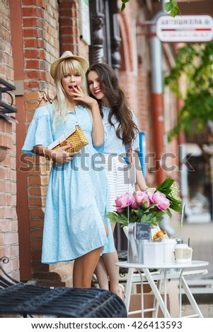 Beautiful brunette and blonde women walk in the street. Make shopping and talking. Day light. Life style.