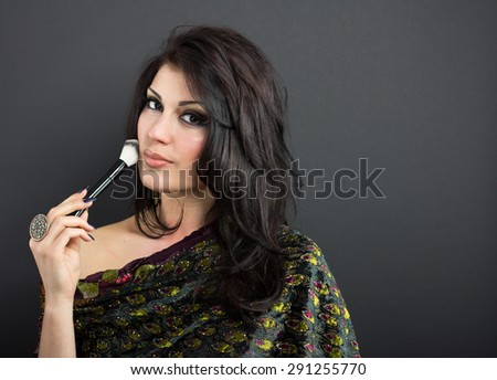 Beautiful brunette apply makeup in bright clothes. Portrait of a well-groomed woman. Attractive brunette with make-up brush - stock photo