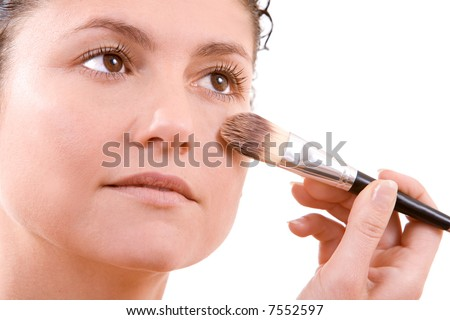 Beautiful brunette applying foundation to her face with a big brush - stock photo