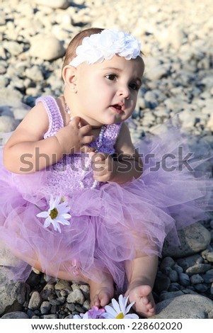 Beautiful brunette baby girl sitting on pebble beach - stock photo