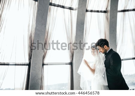 Beautiful brunette bride and bridegroom standing close to each other at big window at background, wedding photo, copy space. - stock photo
