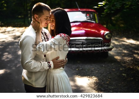 beautiful brunette bride and elegant groom in embroidery costumes hugging near stylish retro red car in the sunlight - stock photo