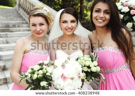 Beautiful brunette bride and gorgeous bridesmaids with bouquets posing near stairs - stock photo