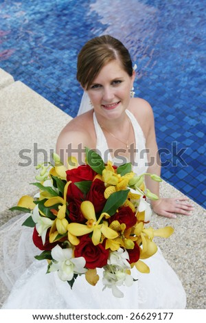 Beautiful brunette bride by the pool on her wedding day.