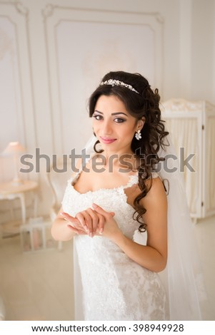 beautiful brunette bride in a luxurious wedding dress posing in interior