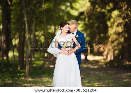Beautiful brunette bride in elegant dress and handsome groom in blue suit at wedding day lovely hugging outdoors on nature. Happy newlywed woman and man embracing in green park. Loving wedding couple. - stock photo