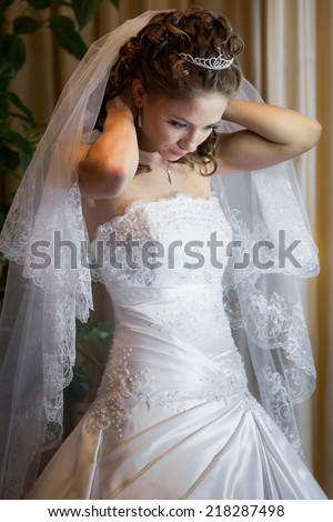 beautiful brunette bride in elegant white dress prepared for her wedding day - stock photo