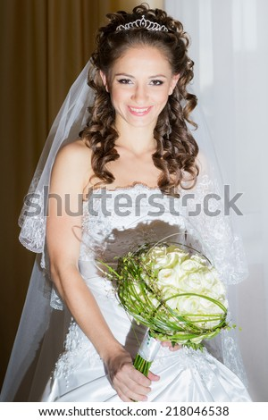 beautiful brunette bride in elegant white dress smile and hold her bridal bouquet in hands - stock photo