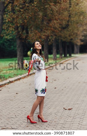 Beautiful brunette bride in traditional ukrainian clothes posing in park with bouquet
