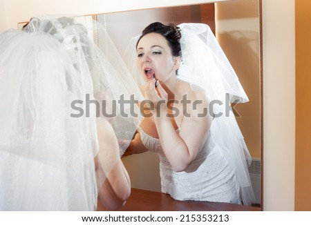 beautiful brunette bride in wedding dress look at the mirror