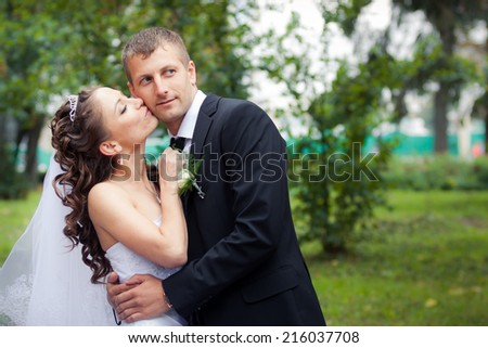beautiful brunette bride in white wedding dress kiss her young handsome groom on green park background