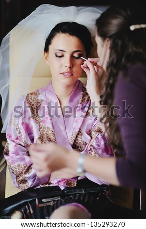 Beautiful Brunette bride is getting ready in the morning - stock photo