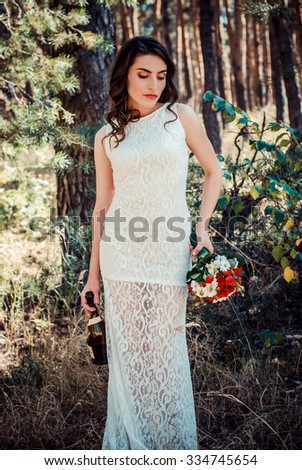 beautiful brunette bride is holding a wedding bouquet and a bottle of champagne - stock photo