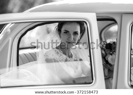 Beautiful brunette bride laughing in luxury white wedding car, window reflection b&w