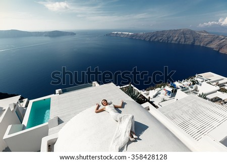 Beautiful brunette bride lying on the terrace in white dress with sea background