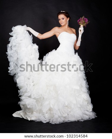 Beautiful brunette bride portrait in studio on black background - stock photo