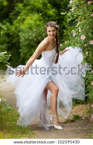 Beautiful brunette bride portrait in summer park - stock photo