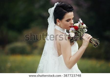 Beautiful brunette bride posing in flower meadow with wedding bouquet - stock photo