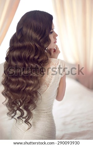 Beautiful brunette bride with long healthy wavy hair styling posing against the window in modern interior.