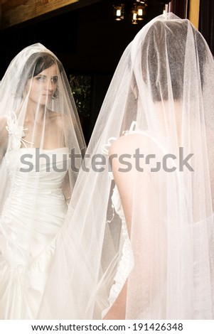 Beautiful brunette bride with short hair and white gown - stock photo