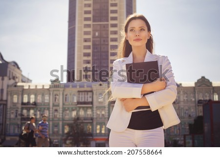 stock photo beautiful brunette business woman in white suit with folder of documents in her hands outdoors 207558664
